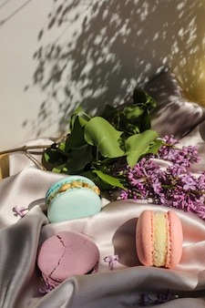 분홍색과 민트 프랑스 마카롱 또는 마카롱 쿠키와 천 배경에 라일락 꽃. 천연 과일과 베리 맛, 발렌타인 데이 부활절을 위한 크림 스터핑, 사랑의 음식.
