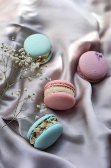 분홍색과 민트 프랑스 마카롱 또는 마카롱 쿠키와 천 배경에 흰색 꽃. 천연 과일과 베리 맛, 발렌타인 데이 부활절을 위한 크림 스터핑, 사랑의 음식.