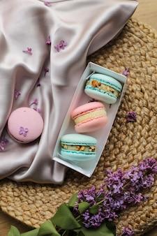 분홍색과 민트 프렌치 마카롱 또는 마카롱 쿠키는 선물 상자에 있고 라일락 꽃은 천과 짚 스탠드 배경에 있습니다. 천연 과일과 베리 맛, 발렌타인 데이, 어머니의 날을 위한 크림 같은 스터핑.