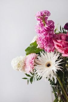 灰色の壁の背景にモダンなガラスの花瓶のピンクとパステルの白い花を垂直にクローズアップ
