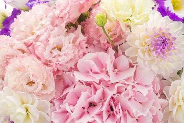 Розовый и фиолетовый букет цветов в розовой коробке, изолированных на белом фоне.