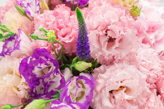 白で隔離されるピンクのボックスに花のピンクと紫の花束。