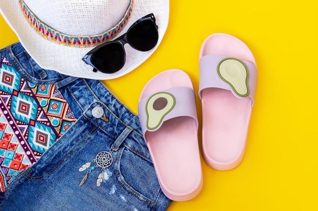 Розовые и фиолетовые женские пляжные шлепанцы с половинками авокадо, джинсовые шорты с узором в стиле бохо, черные солнцезащитные очки и белая шляпа ловца снов на стене желтого цвета