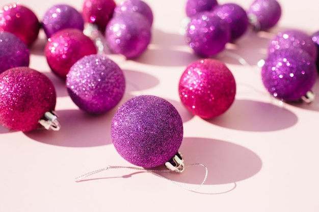 분홍색 배경에 분홍색과 보라색 반짝이 크리스마스 볼 장식. 새해 인사말 카드.
