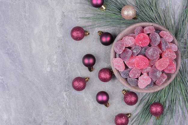 Розовые и фиолетовые мармелады в деревянной чашке