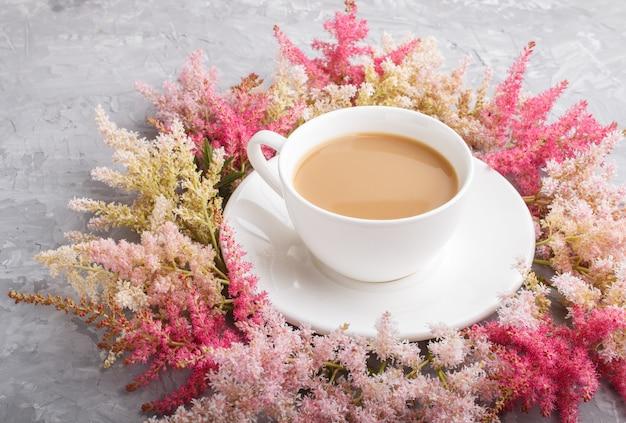 Розовые и красные цветы астильбы и чашка кофе на сером бетонном фоне