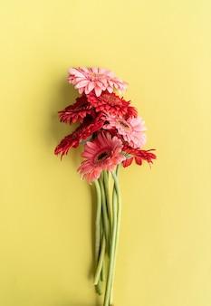 緑の背景にピンクと赤のガーベラの花束。ミニマルデザインフラットレイ