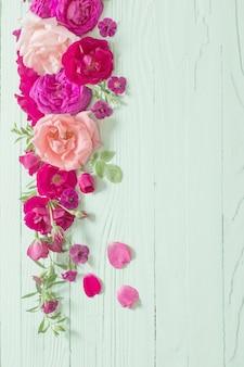 緑の木製の背景にピンクと赤のバラ