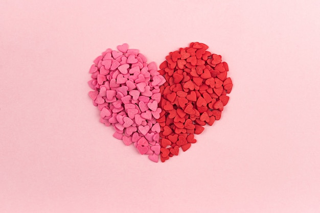 Розовые и красные конфеты в форме сердца дня святого валентина на пастельной предпосылке. плоское положение, текстура сердец вида сверху. концепция любви. святой валентина, поздравительные открытки ко дню матери, приглашение.