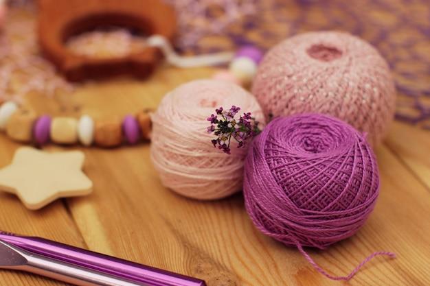 Шарики и крючки из пряжи для вязания крючком розового и фиолетового цветов.