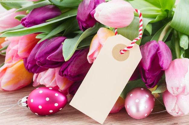 イースターエッグと白紙のノートとピンクと紫のチューリップ