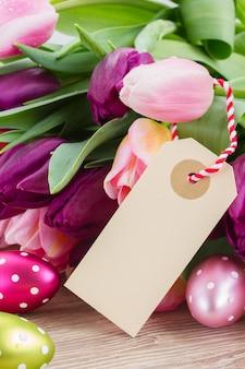 イースターエッグと空の紙のメモとピンクと紫のチューリップ