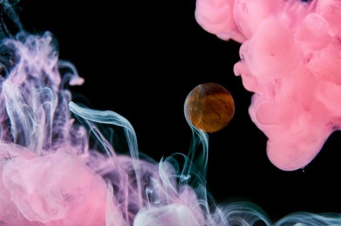 검정색 배경에 물에 분홍색과 흰색 아크릴 잉크가 유리 공을 둘러싸고 있습니다. 추상적 인 배경입니다.