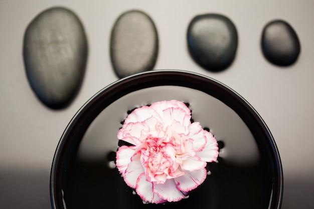 ピンクと白のカーネーションは黒いボールの上に浮かんでおり、その上に揃えられた黒い石が