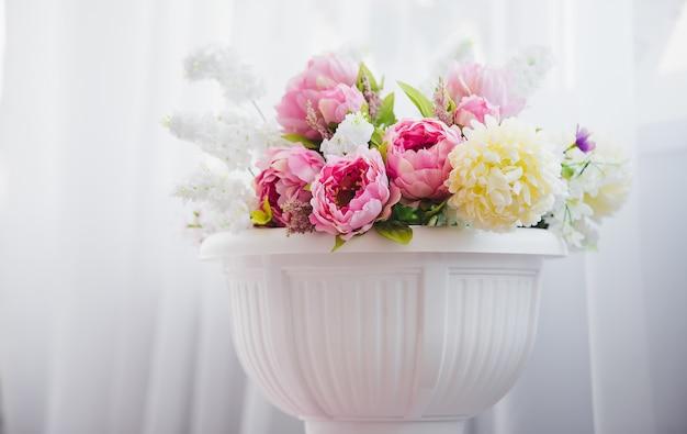 Розовые и белые цветы в вазе возле кровати