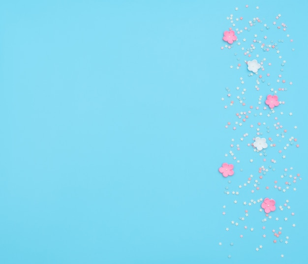 Розовые и белые цветы из фоамирана с конфетти в форме звезды на синем фоне.