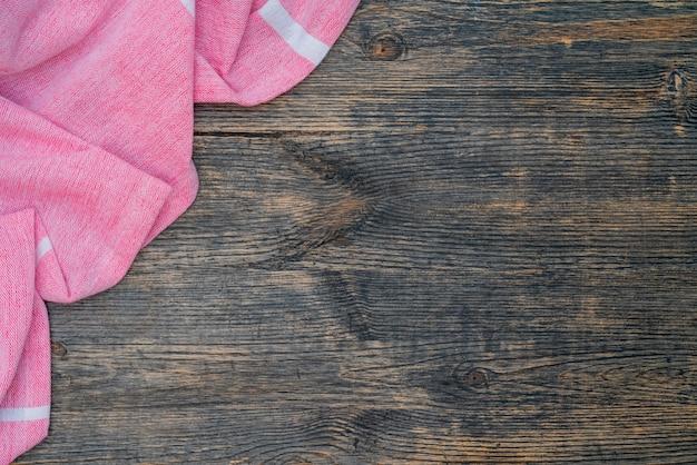 Розовое и белое кухонное полотенце лежит на деревянном столе. текстура крашеного дерева. фактурные складки ткани.