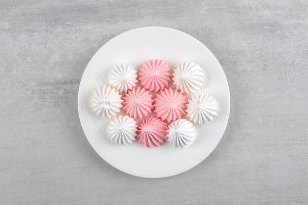 Розово-белое безе на белой тарелке на мраморном столе.