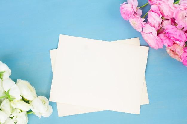 白紙のノートの青い木製の背景にピンクと白のラナンキュラスの花