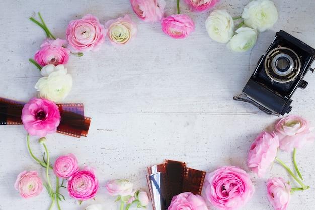 ピンクと白のラナンキュラス新鮮な花とレトロなカメラフラットレイシーン、木製デスクトップ上のコピースペース