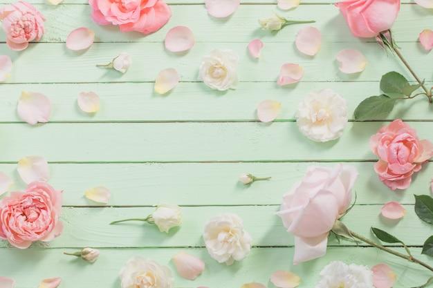 緑の木製の背景にピンクと白のバラ