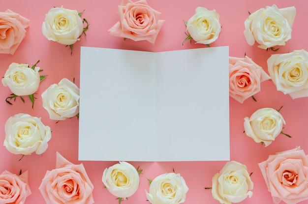 Розовые и белые розы на розовом фоне с пустой белой карточкой на день святого валентина