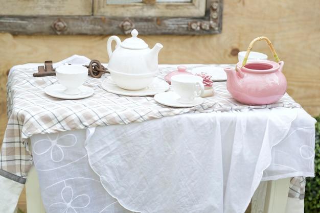 서비스 차 또는 커피 아침 식사를 위해 준비된 테이블에 분홍색과 흰색 차 세트