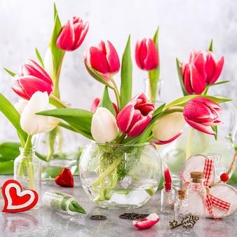 밝은 회색 표면에 유리 화병에 분홍색과 흰색 튤립. 발렌타인 데이 선물. 어머니의 날 인사말 카드
