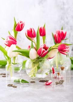 밝은 회색 표면에 유리 화병에 분홍색과 흰색 튤립. 여성의 날 선물. 어머니의 날 인사말 카드