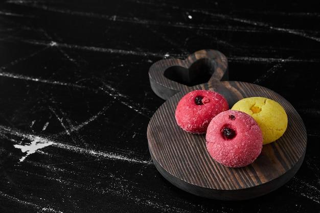 Розовое и желтое печенье на деревянной доске.
