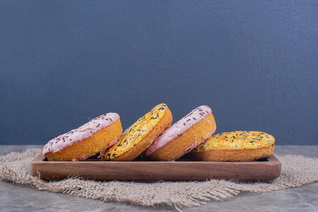 Розовые и желтые кремовые пончики на деревянном блюде