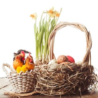 Розовые и желтые яйца в корзине, пасхальные украшения на белом фоне