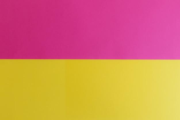 テキスト用のスペースがあるピンクと黄色のパステルカラーの紙の表面