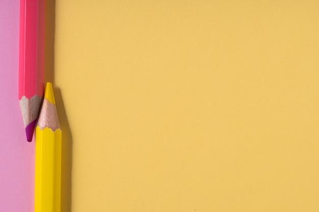 Розовые и желтые карандаши на пастельно-розовом и желтом контрастном фоне. концепция образования. вид сверху. место для текста