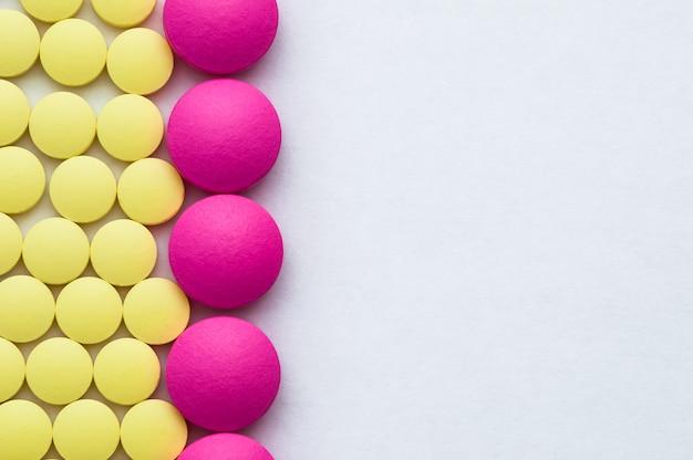 Розовые и желтые пилюльки в ряд на белой предпосылке.