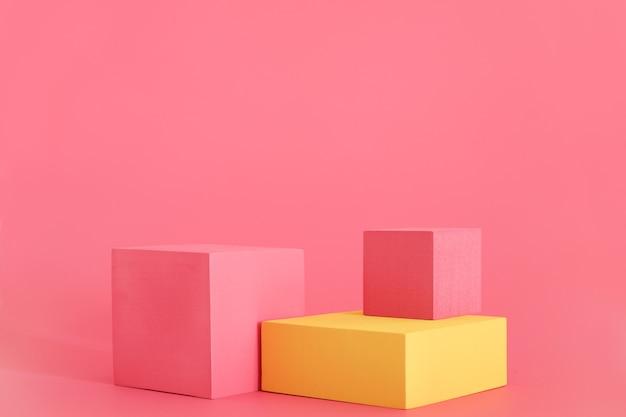 분홍색 배경에 분홍색과 노란색 연단입니다. 제품 연단, 화장품 프레젠테이션. 창의적인 모의. 미용 제품을 위한 받침대 또는 플랫폼.