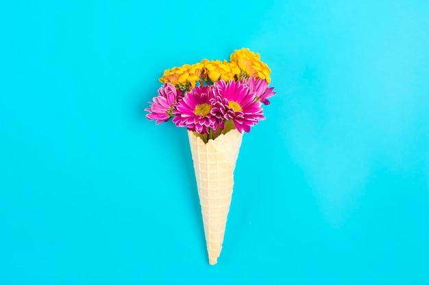青い背景の上のアイスクリームワッフルコーンのピンクと黄色の春の花デイジー