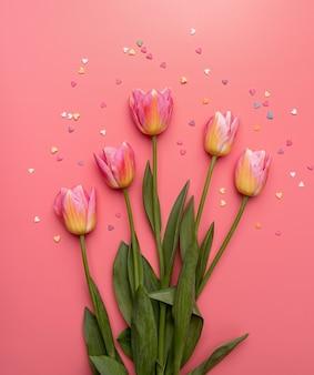 분홍색 배경에 작은 심장 모양으로 장식 된 분홍색과 노란색 튤립 평면 누워 복사 공간 평면도