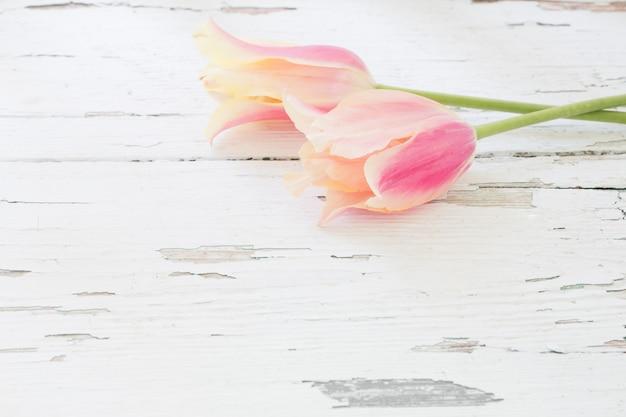 塗られた木製の背景にピンクと黄色のチューリップ