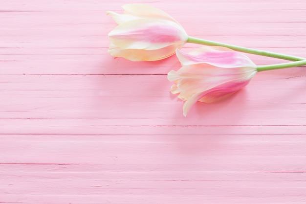 塗られた木の表面のピンクと黄色のチューリップ