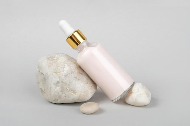 ピンクのアンチエイジングコラーゲン、透明なガラス瓶に入ったフェイシャルセラム、ゴールドのピペット、グレーの天然石
