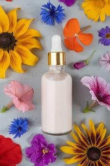 회색 배경에 있는 유색 꽃들 사이에 분홍색 노화 방지 콜라겐, 얼굴 혈청 또는 기타 화장품이 유리병에 들어 있습니다. 천연 유기농 스파 코스메틱 개념 모형 평면도.