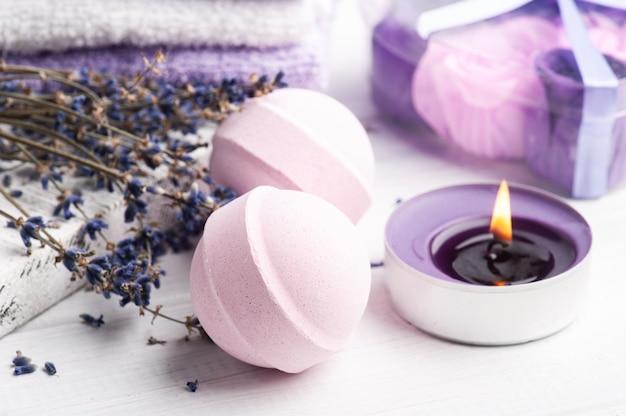 ドライラベンダーの花とタオルを備えたスパ構成のピンクのアロマバスボム。アロマテラピーのアレンジ、キャンドルを灯した禅の静物