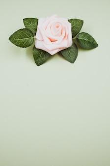 Розовая искусственная роза на зеленой поверхности