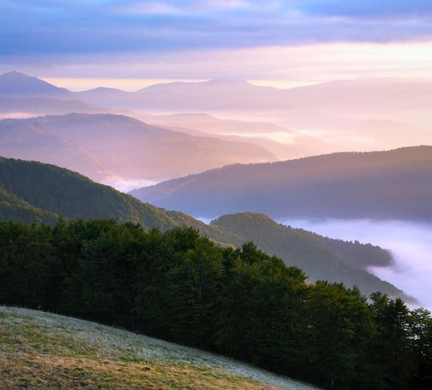 Розовое осеннее утро с видом на горы с солнечным лучом и дымкой