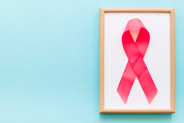 Pink awareness ribbon on white frame over the blue background
