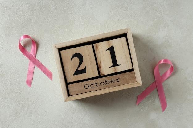Розовые ленты осведомленности и деревянный календарь с 21 октября на белом текстурированном фоне