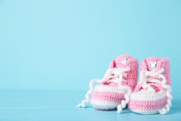 Pink baby booties on blue  with copy space