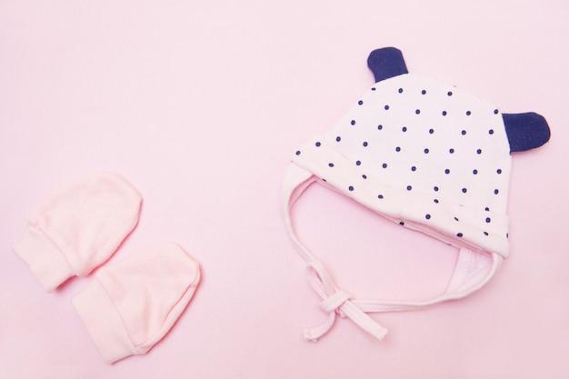 ピンクの赤ちゃんコアフとミトン。ピンクの背景の上面図の小さな女の子のための服