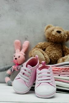 ピンクの赤ちゃんの女の子の靴、新生児服、柔らかいおもちゃ。コピースペースを持つ母性、教育または妊娠の概念。
